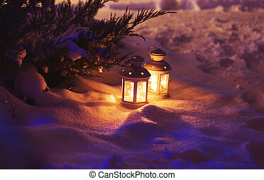 Two Lantern with burning candle on snow in the evening....
