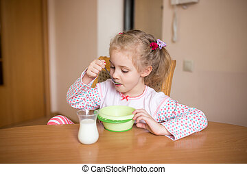 Little girl having breakfast at home. Milk mustache - Little...