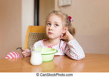Little girl having breakfast at home Milk mustache - Little...