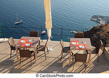 Alfresco cafe on terrace over sea coast, Santorini, Greece -...