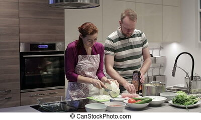 Woman and man cut vegetables in the kitchen