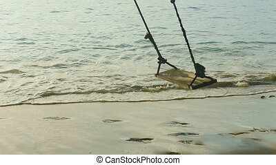 A rope swings on the beach, slow motion - A rope swings on...