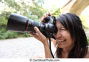 pretty female photographer taking photos with her modern...