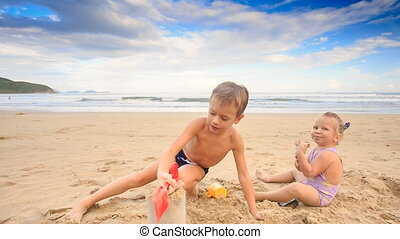 Kids Small Girl Boy Gambol Play with Wet Sand on Beach - two...