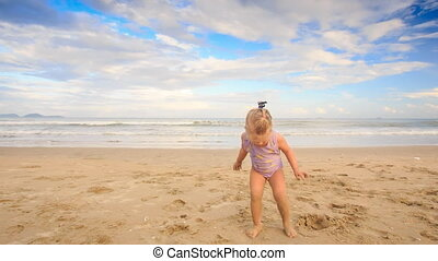 Upset Small Girl with Pigtail Shows Dirty Hands on Sand Beach
