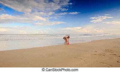 Little Blond Boy Kicks Red Ball on Wet Sand Beach