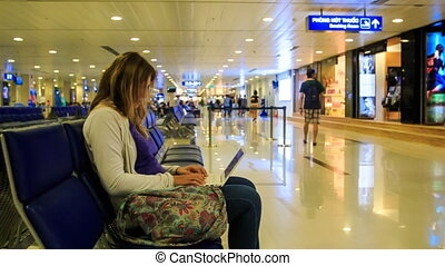 Blond Girl Sits on Waiting Chair Works on Laptop inTerminal