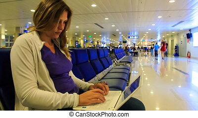Closeup Blond Girl Tapes Text on Laptop in Airport Terminal...