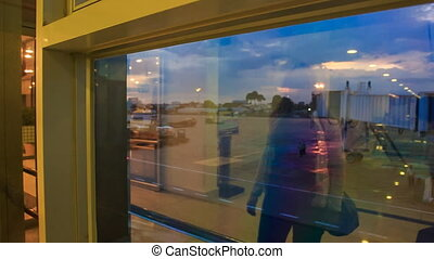 Backside Girl Watches Evening Airport Reflection in Window -...