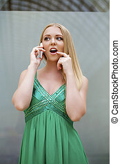 Young beautiful girl in the green dress talking on cell...