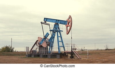Work of oil pump jack on a field.