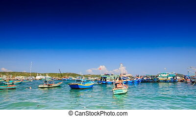 Distant View of Vietnamese Fishing Boats in Bay against Sky...