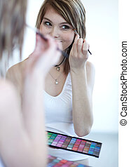 pretty young woman applying mascara eyeshadows in front of a...