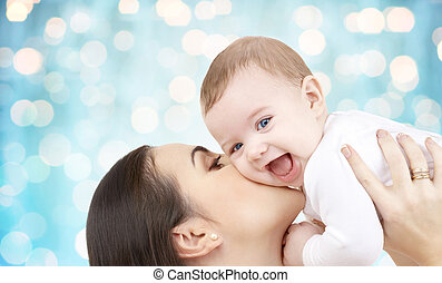 happy mother kissing her baby over blue lights - family,...