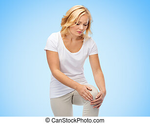 unhappy woman suffering from pain in leg - people,...