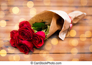 close up of red roses bunch wrapped into paper - love, date,...