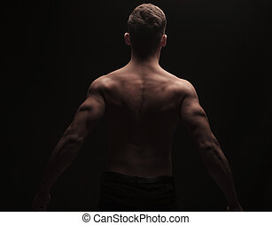 rear view of muscular man flexing his back and arms in dark...