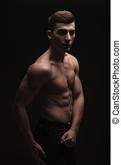 fit handsome man side posing in dark studio background while...