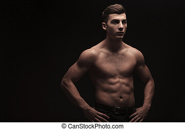 young male flexing in dark studio background with hands on waist