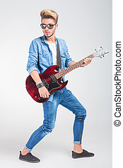 artist playing guitar in studio while posing looking away -...