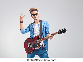 artist posing in studio holding a guitar and showing the...