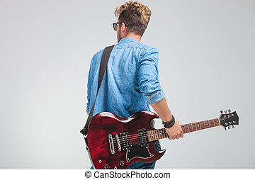 rear view of young artist holding a guitar in studio - rear...