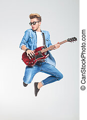 guy wearing sunglasses jumping in studio while playing...