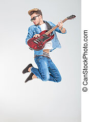 male artist jumping in studio while playing guitar and...