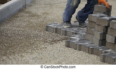 Worker puts paving - Worker puts the correct paving
