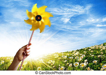 Spring Wind - Children hand holding a yellow windmill in a...