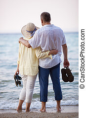 Couple embracing and looking at sea - Back shot of man and...
