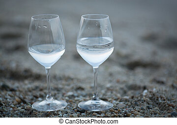 Two glasses of water on the beach - Two glasses of fresh...