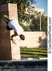 Young man performing parkour in the city - Young athlete...