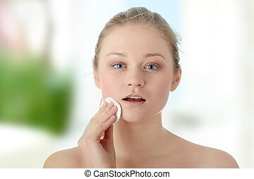 Woman remove her make-up - Young woman using a cotton pad to...