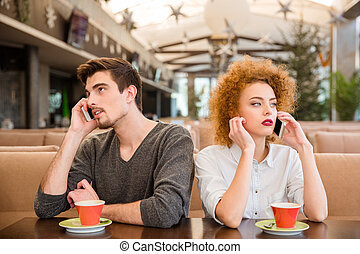Man and woman talking on the phones in restaurant - Portrait...