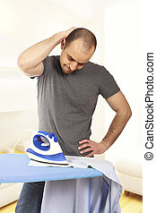 single man lifestyle - young man try to ironing his clothes...
