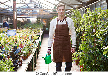 Smiling man gardener standing and holding watering can in...