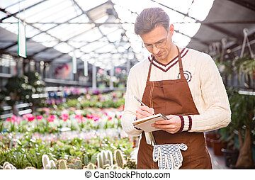Consentrated male gardener writing in notepad - Consentrated...