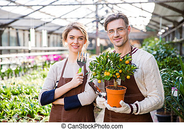Happy attractive woman and man gardeners holding small...