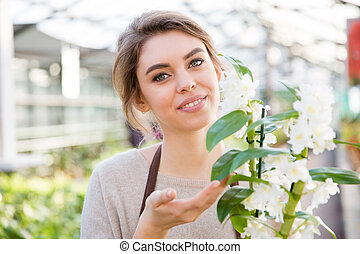 Pretty woman gardener with white blooming orchid in orangery...