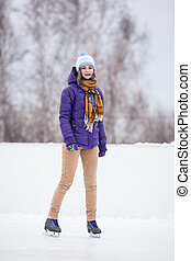 Young woman skating on ice with figure skates - Ice skating...