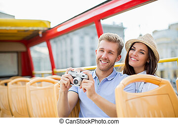 Tourism - Young couple in a tourist bus...