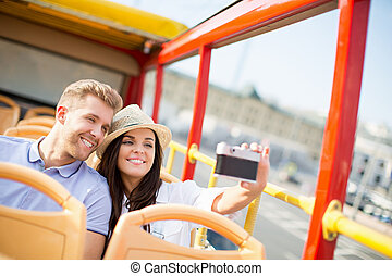 Tourist - Young couple in a tourist bus makes selfie