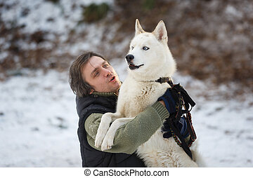 Man embracing with husky dog - Man embracing with husky in...