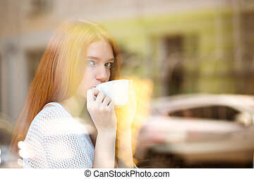 Woman drinking coffee and looking at window