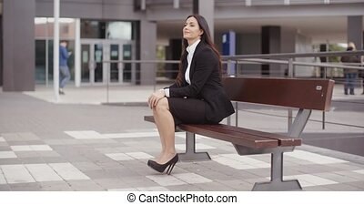 Calm business woman sitting outdoors - Confident young...