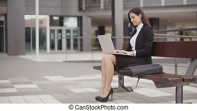 Woman sitting with laptop on bench outdoors - Cute business...