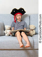 Little girl in pirate costume reading book with her plush...