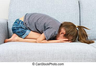 Sad little girl crying on the sofa.
