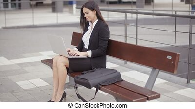 Woman looking over with laptop on bench - Cute business...